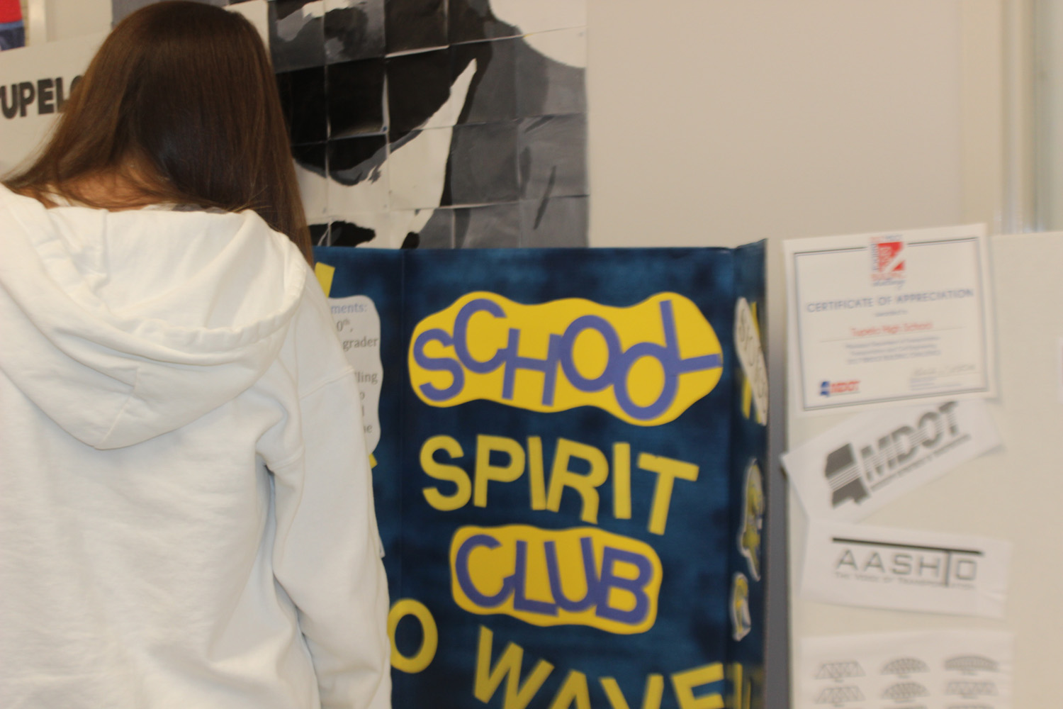 Student engaged in one of the boards at to the Club Fair and the information it holds.