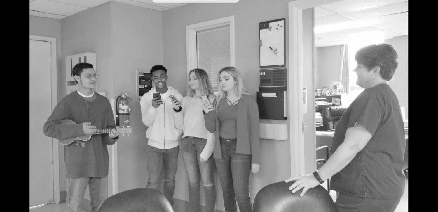 Senior Cole Herrington plays the Ukelele with Malik Small, Claire Burroughs and Cate Burroughs as they seranade a lucky valentine.
