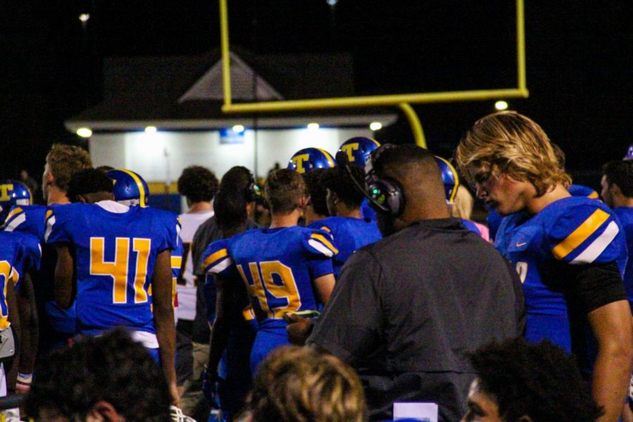 Quarterback Jake Weir goes over strategy and game plans with Coach Jackson during a defensive play.