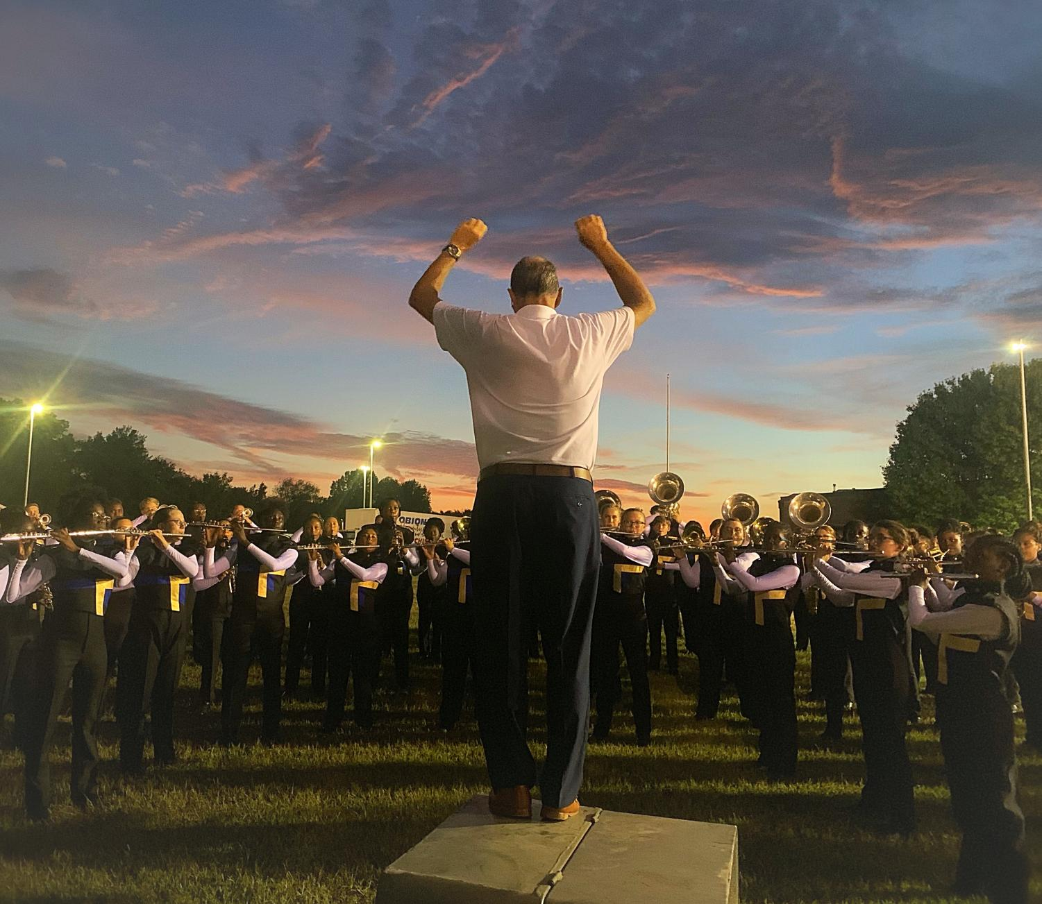 Band Director Rick Murphy warms the band up in a practice field before the competition.